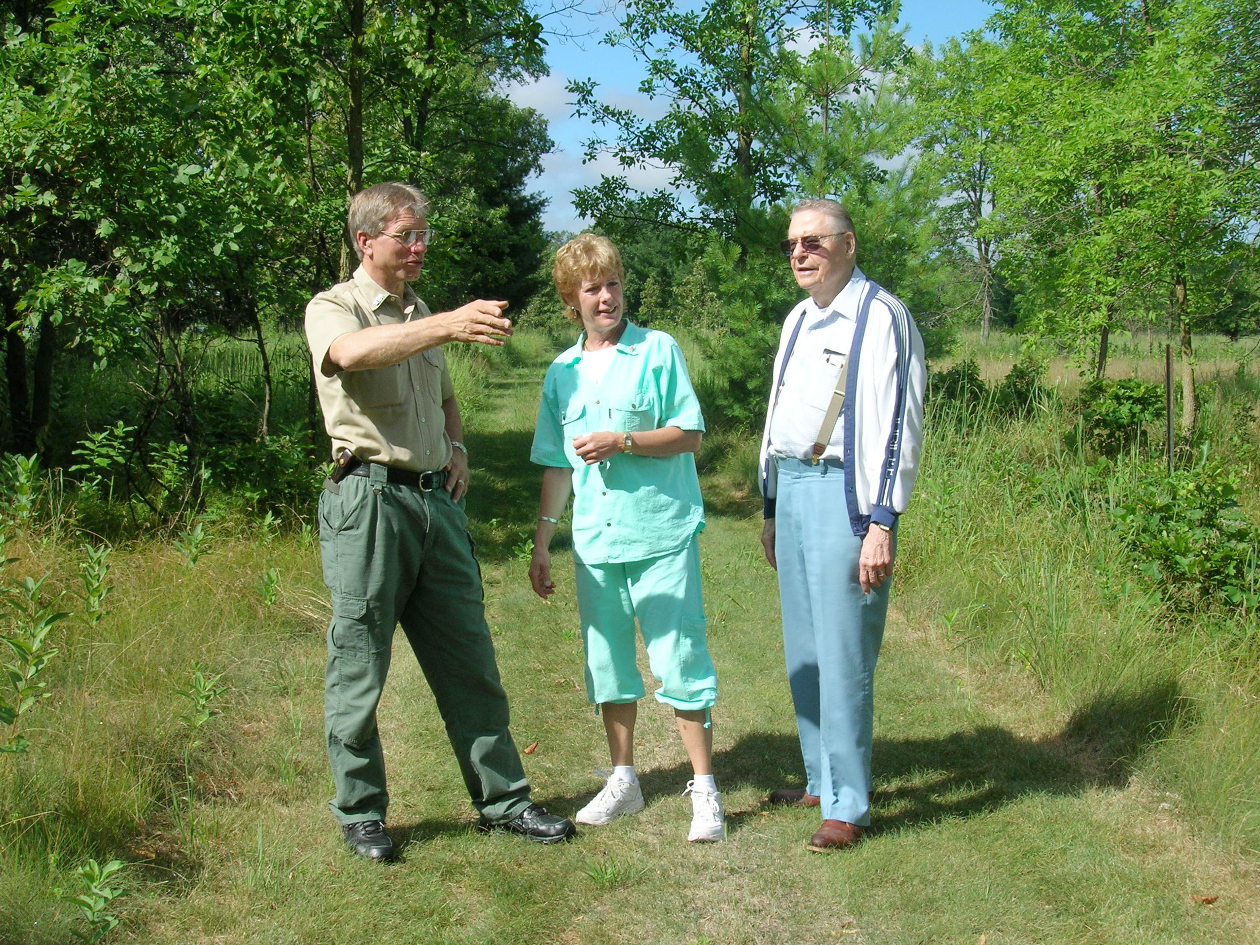 Park staff points while talking to two people