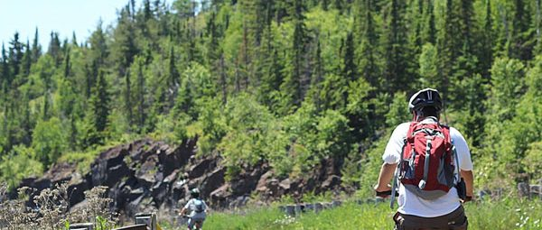 Biker with pine trees and exposed rock in background
