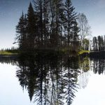 Crystal clear lake reflecting pine trees wtih stars