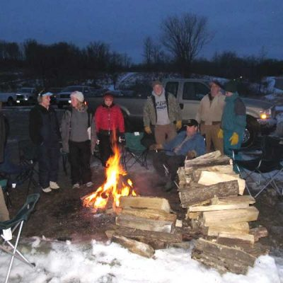 Park visitors gathered around campfire during candlelight ski event