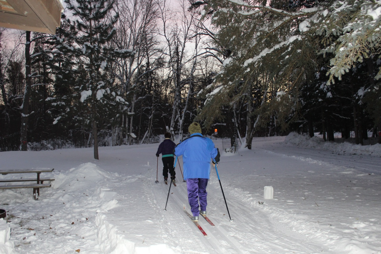 two skiers head down the trail