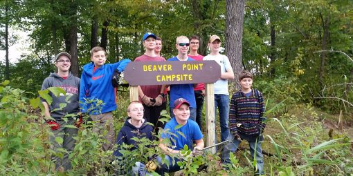 boy scouts pose with a campsite sign