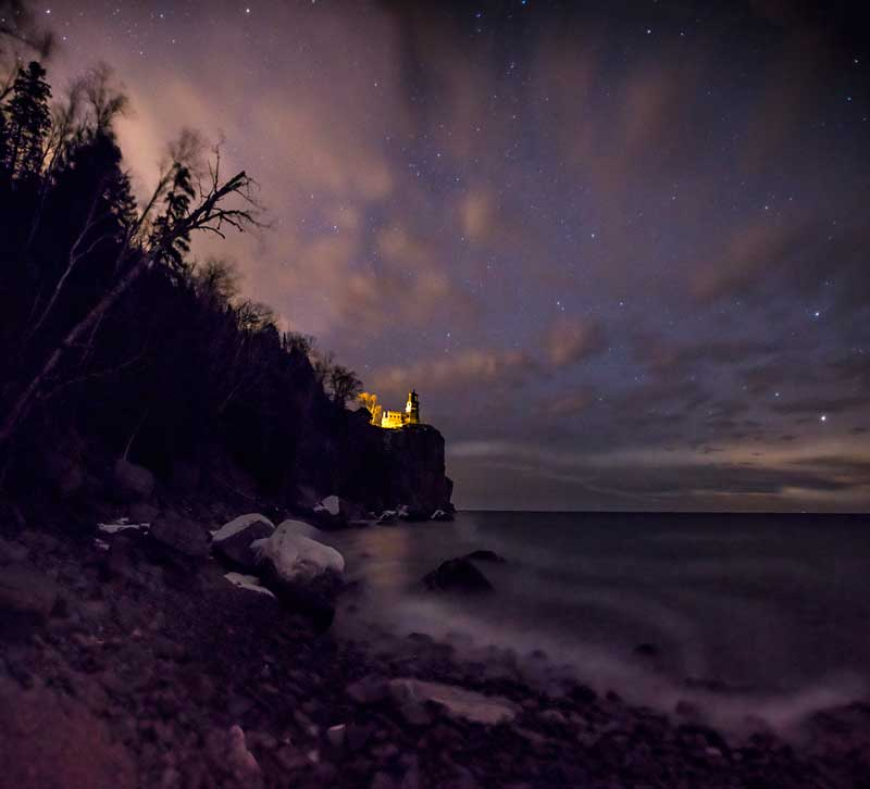 Purple sky with Split Rock Lighthouse lit up on the cliff