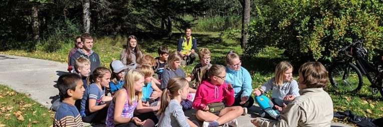 kids sit in meditation with park ranger outside