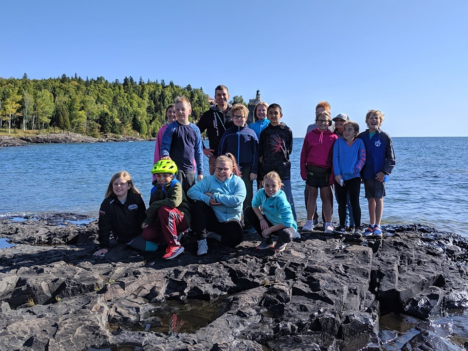 group picture by lake superior with lighthouse in background