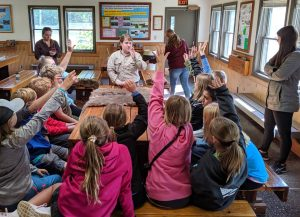 kids raise hand to answer question asked by park ranger