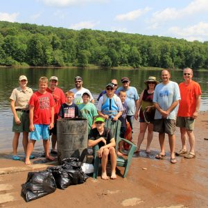 Group of volunteers by St. Croix River and garbage they cleaned up