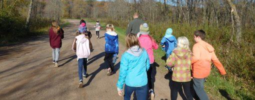 kids and naturalist walk along a gravel path