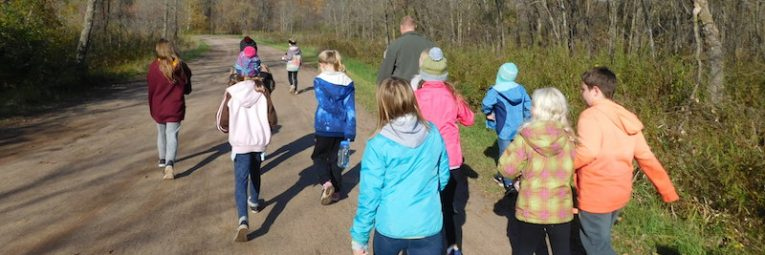 kids and naturalist walk along a gravel path