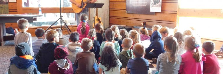 kids sitting on floor in rapt attention to the musician