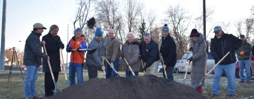 Ten people dig their shovels into a pile of dirt for the ground breaking ceremony