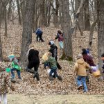 kids running into the woods to find easter eggs