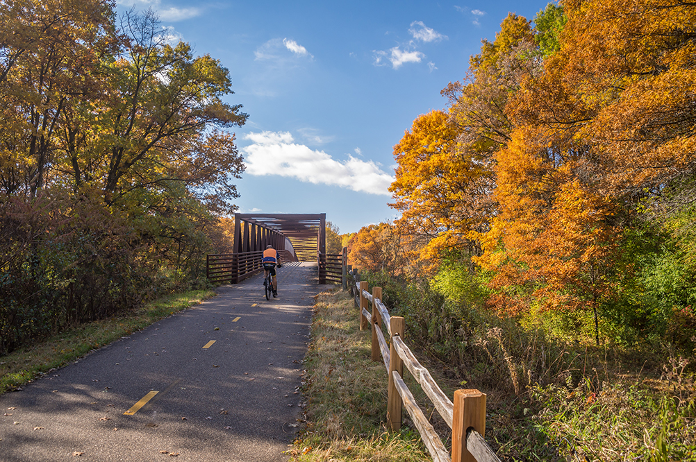 Bicyclist on paved trail approaching a bridge
