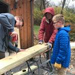 three volunteers building a bench