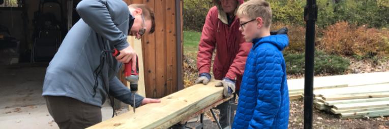 three volunteers building a bench