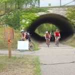 Bicyclists going through tunnel on Glacial Lakes State Trail in New London