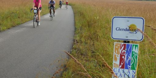 bikers on trail through prairie with Glendalough Trail sign and Legacy sign