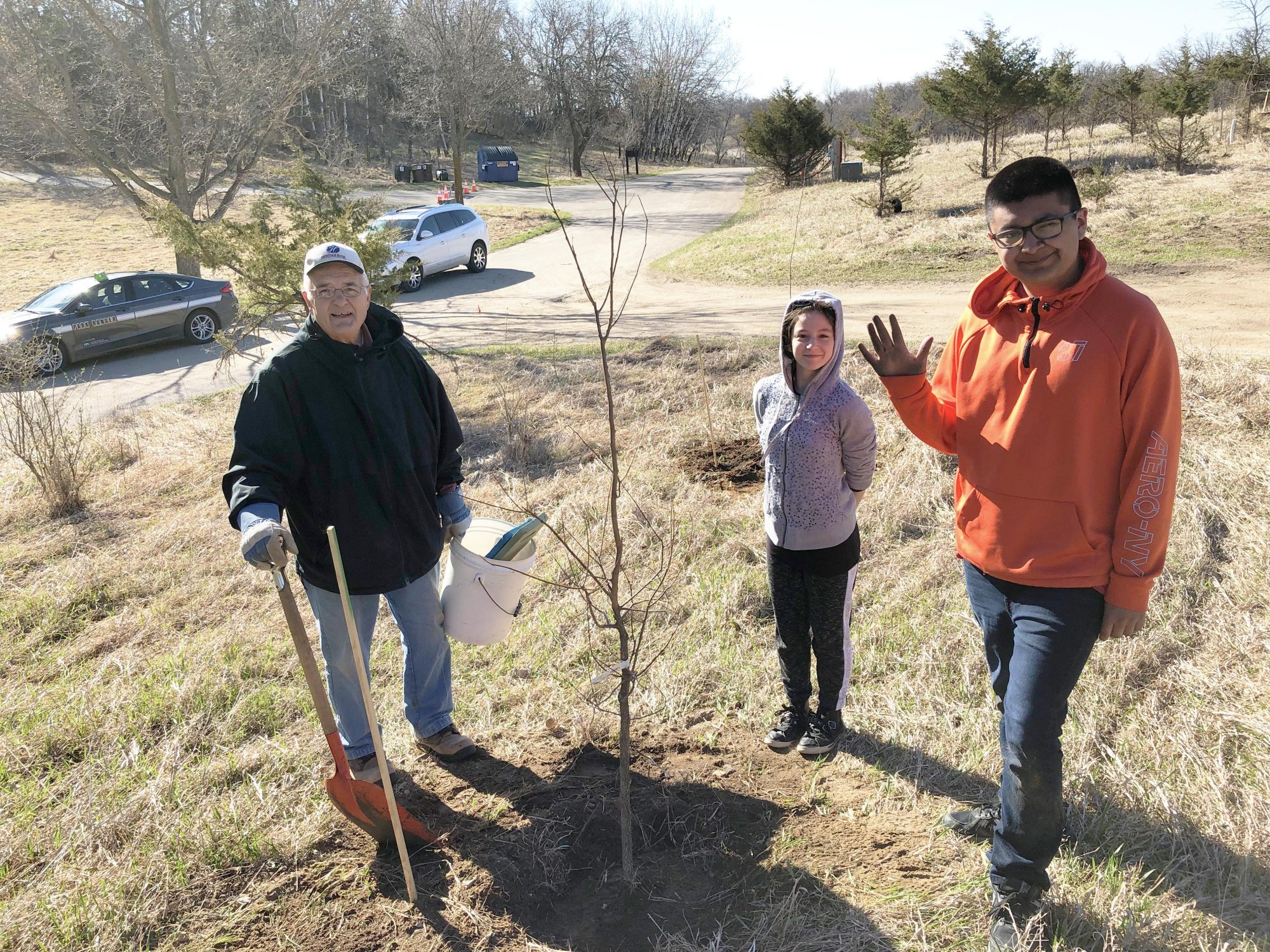 kids and a friends volunteer celebrate having planted a tree