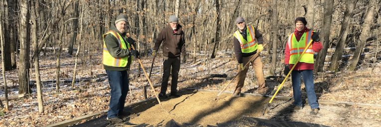 volunteers rake pea rock in a campsite