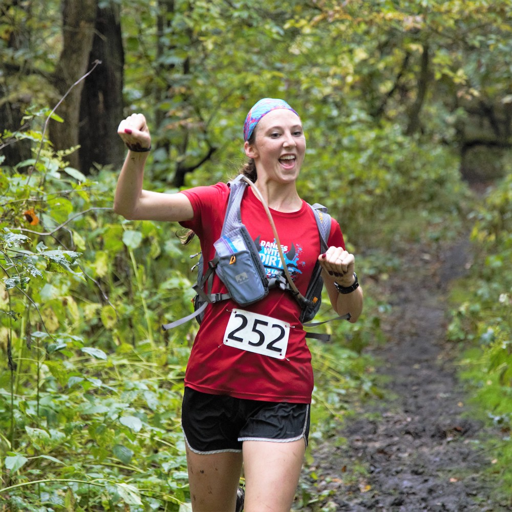 woman fist pumps while trail running in race