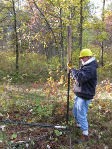 volunteer pounding in a t-post