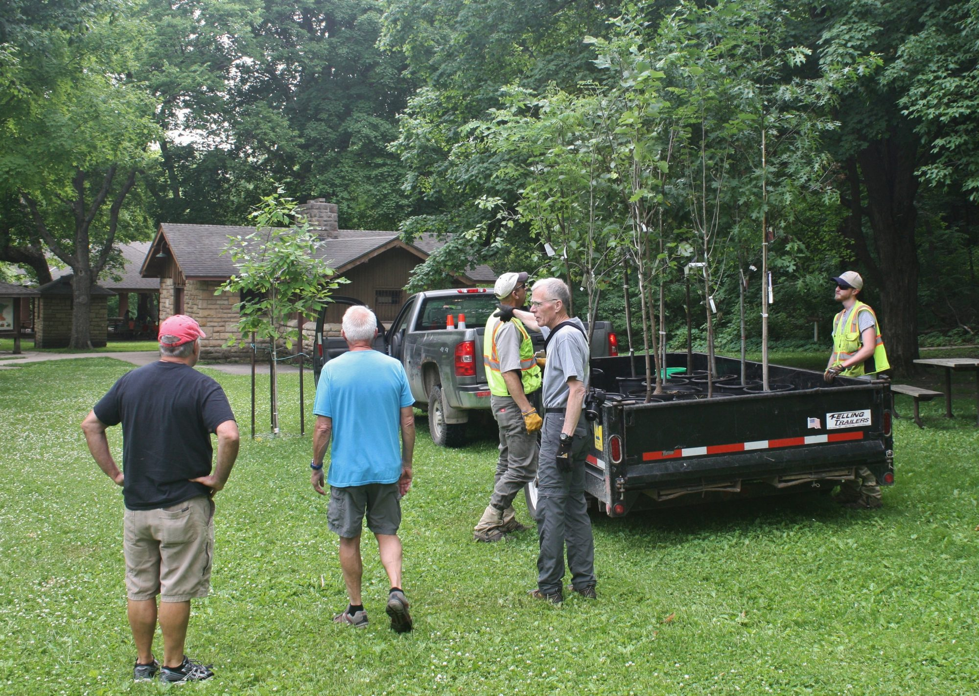 volunteers get ready to unload trees from trailer