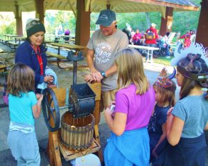 volunteer shows kids how to use an apple press