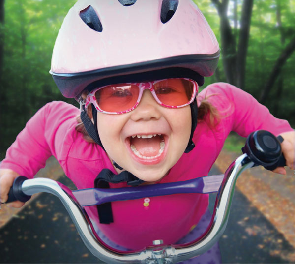 Young girl in pink smiling big on her bike