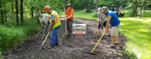 Volunteers raking dirt to restore prairie plants