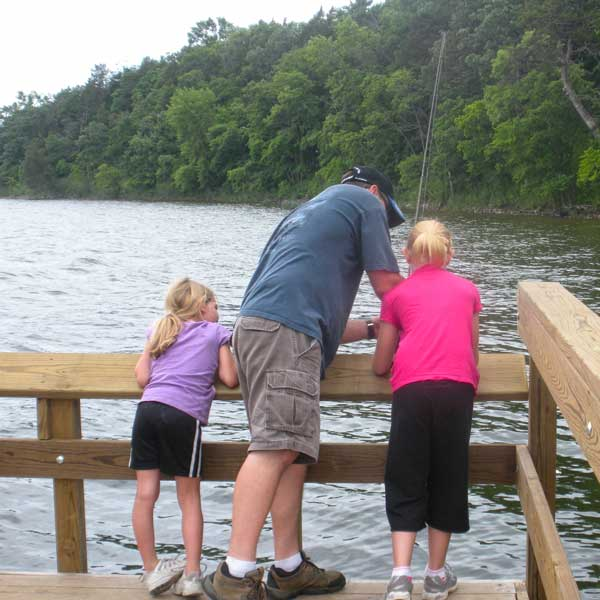Two girls fishing on a pier with their dad