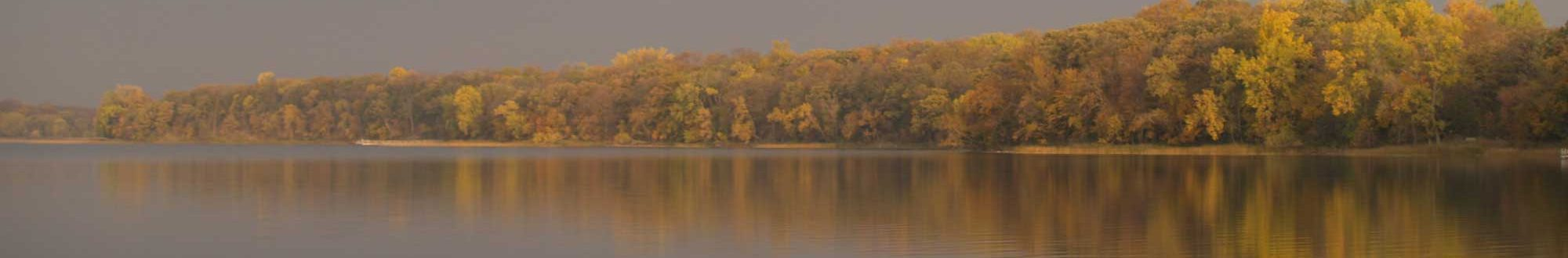 Foggy lake reflecting autumn trees at Sibley State Park