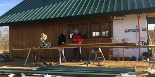 Workers putting up the siding on the sugar shack