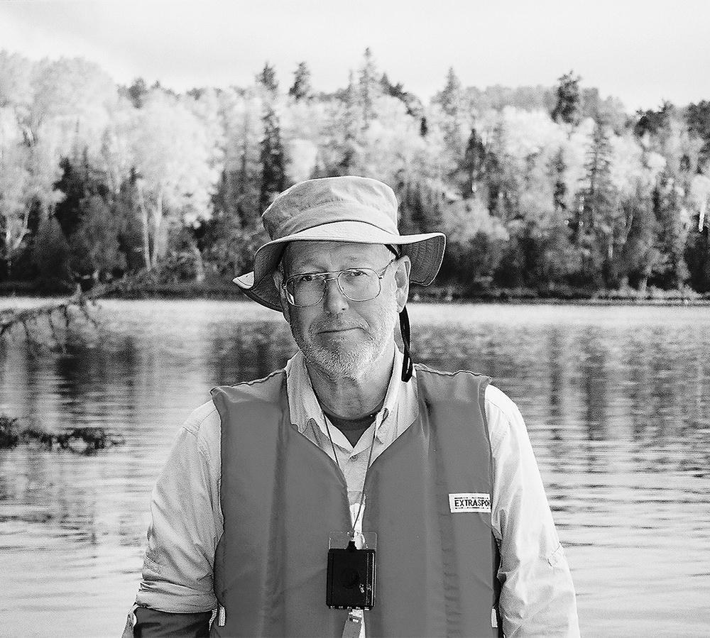 man in fishing cap standing by lake