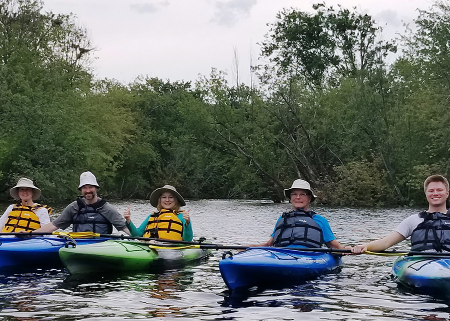 five people in kayaks on river