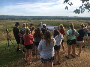 Bison ambassador volunteer speaks with kids at overlook