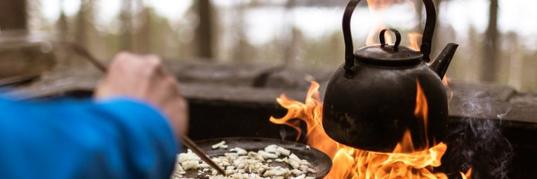Black kettle pan on campfire