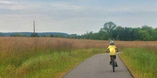 boy biycling along trail