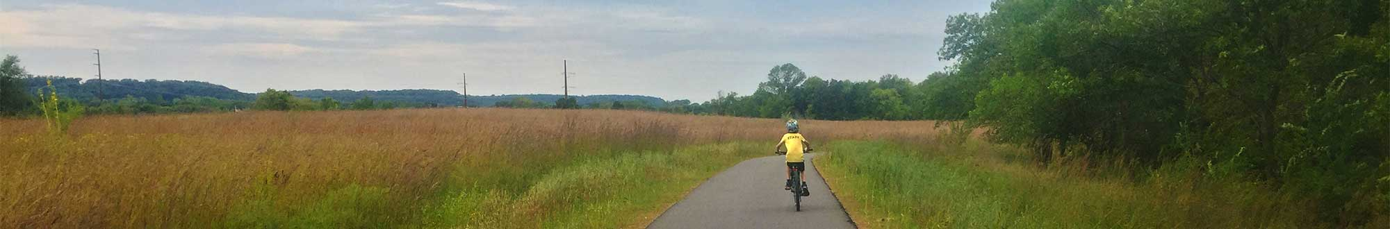 boy biycling along trail
