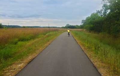 Boy biking trail through grasslands