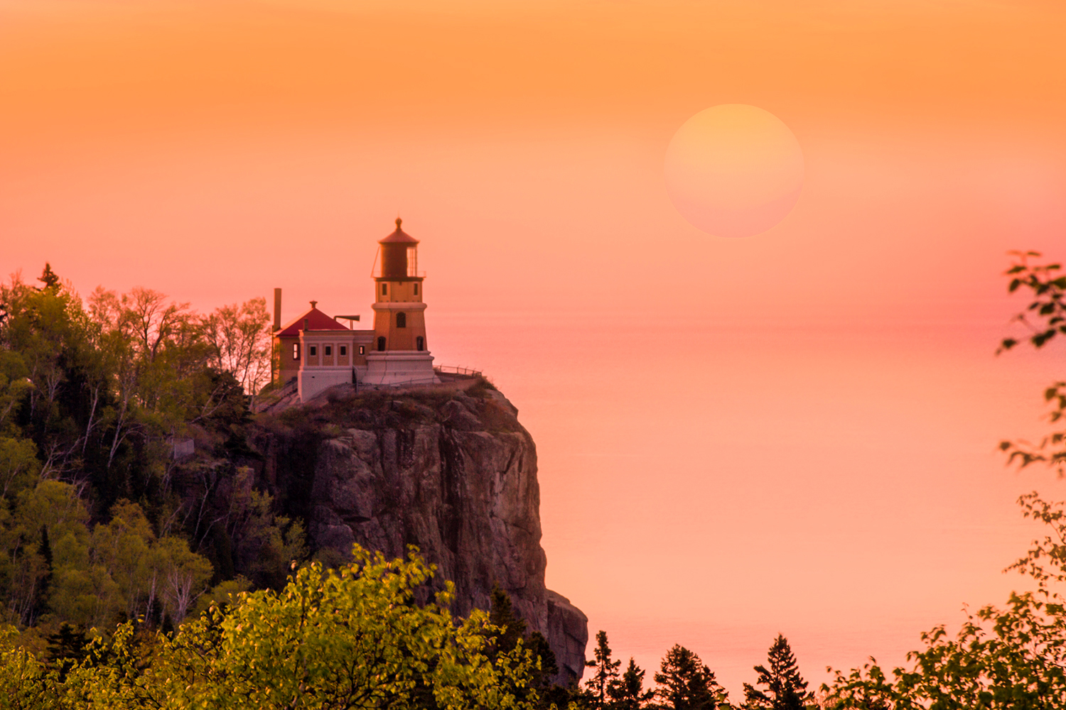 Lighthouse on cliff against pink sky