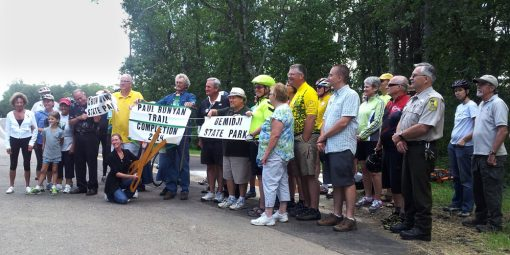 Group celebrating a ribbon cutting for the Paul Bunyan Trail