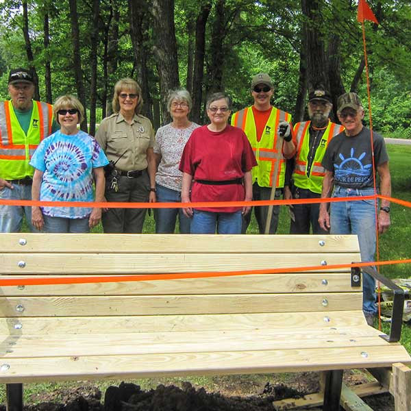 Friends standing by newly installed park bench