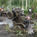 ATV rider flipping vehicle in the mud
