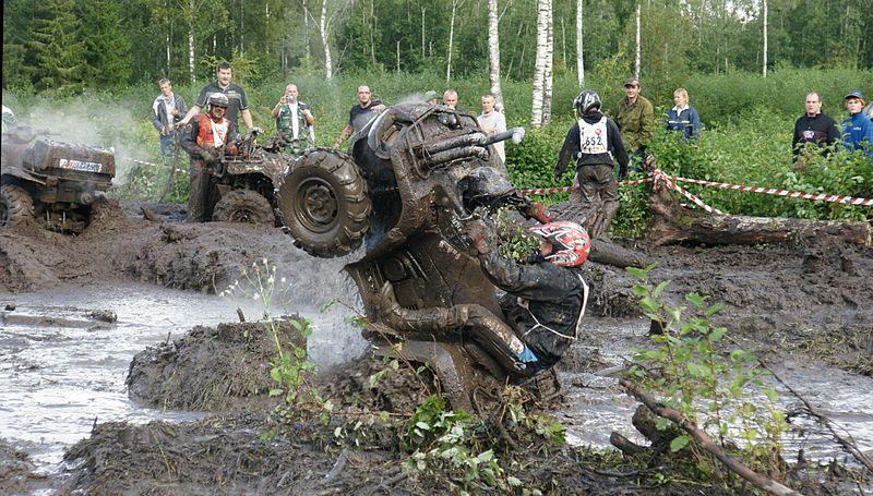 ATV rider flipping vehicle in the mud
