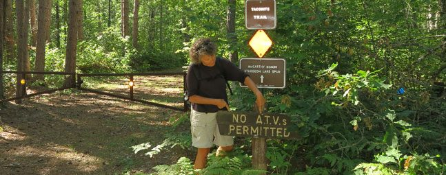 "Woman pointing to ""No ATVs Permitted"" sign along Taconite State Trail"