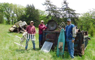 Three men putting trash in dumpster