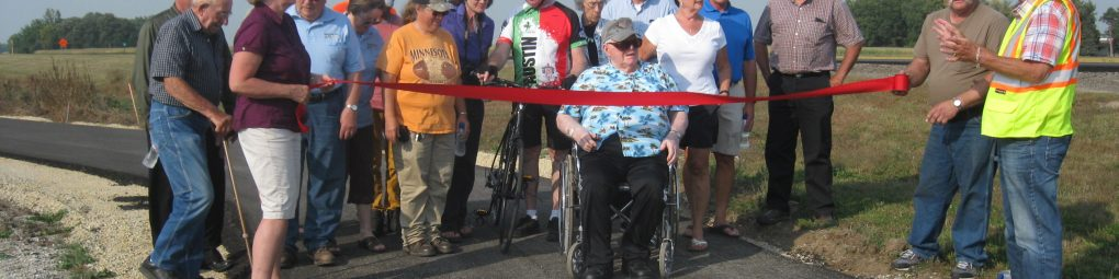 Group cutting ribbon on new segment of Shooting Star State Trail