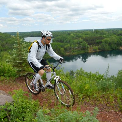 Mountain biker on trail overlooking lake