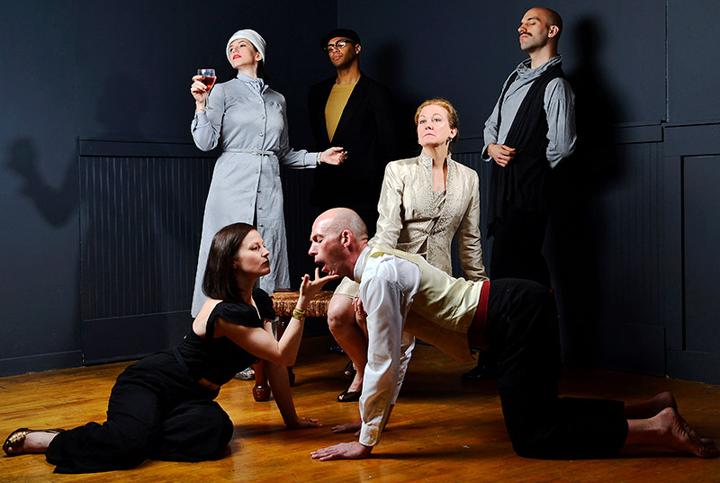 group of actors posing theatrically on stage