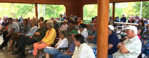a crowd in the picnic shelter enjoys the music